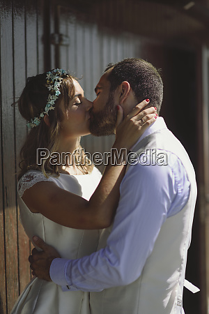 kissing bridal couple in front of