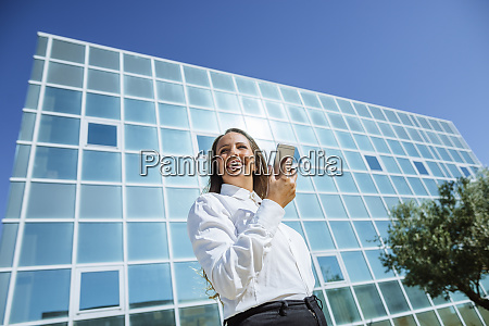 smiling businesswoman using cell phone outside