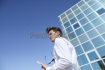 geschaeftsmann mit tablet und sonnenbrille ausserhalb