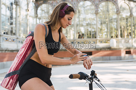 fit young woman carrying yoga mat