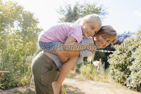 happy mother carrying daughter piggyback in
