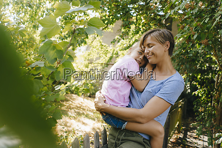 happy mother carrying daughter in garden