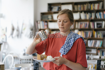 young woman serving plate with cake