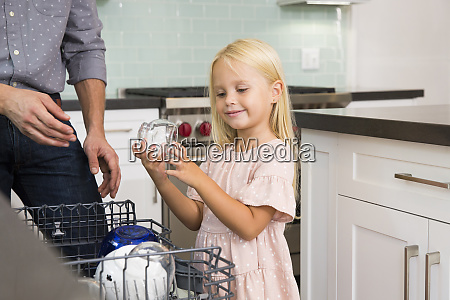 girl helping father clearing the dishwasher