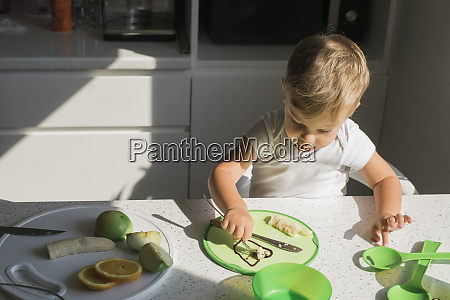 little boy sitting at table in