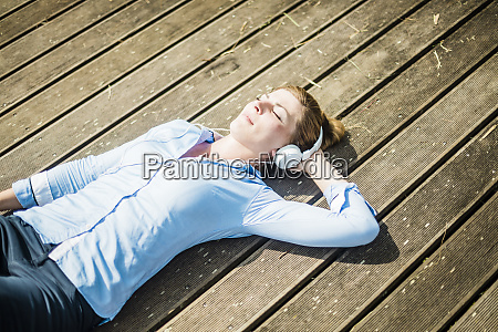 woman lying on planks wearing headphones