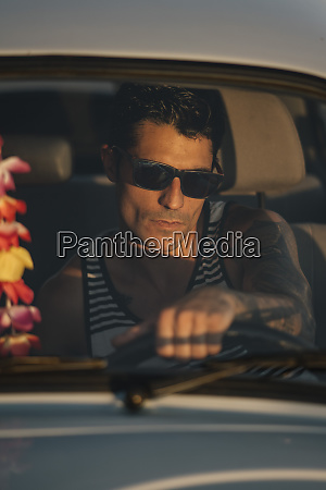 cool man wearing sunglasses driving a