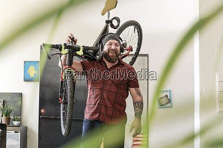 laughing man wearing headphones carrying bicycle