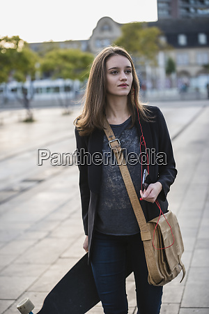 young woman with longboard and cell