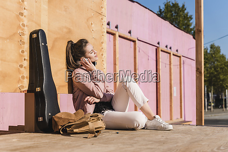 smiling young woman sitting on platform