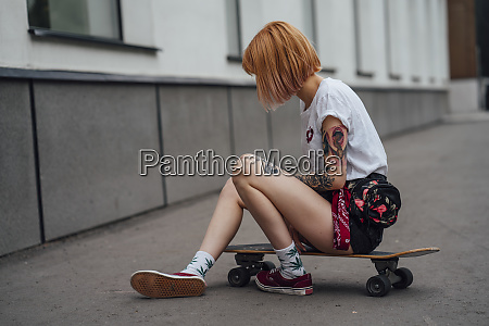 young woman sitting on carver skateboard