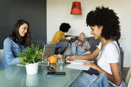 women using laptop and notebook at