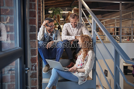 young business people sitting on stairs