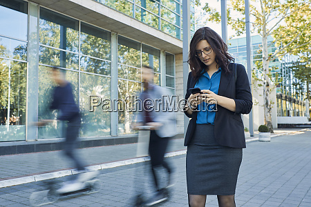 businesswoman using cell phone with commuters