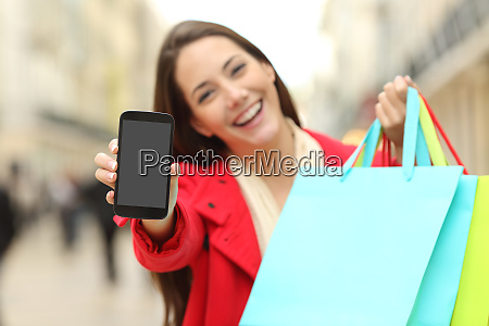 shopper with shopping bags showing phone