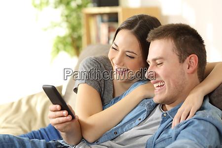 ehepaar lacht beim anschauen von medieninhalten