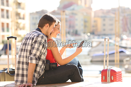 couple of tourists checking phone content