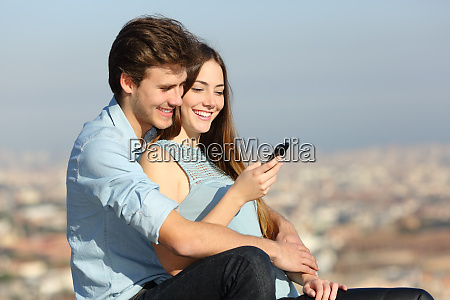 happy couple checking phone sitting in