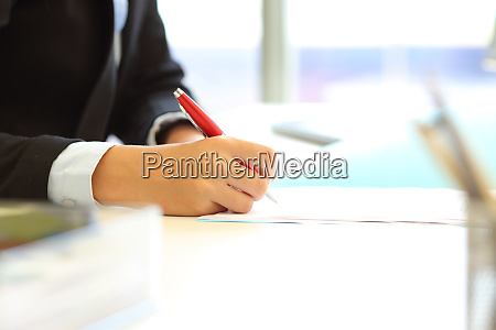 office worker hand signing contract or