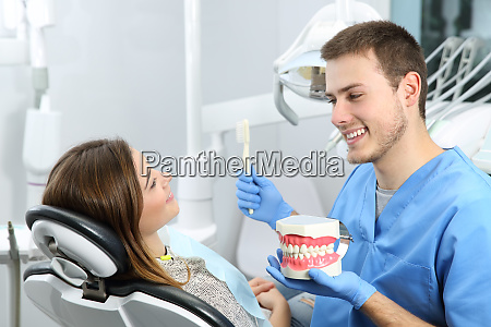dentist explaining teeth brushing procedure to