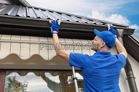 man installing house roof rain gutter