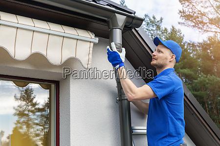 worker installing house roof rain gutter