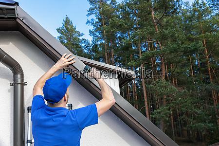 dachdecker installiert metalltropfrandprofil auf dem hausdach