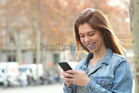 happy teenager texting on phone walking