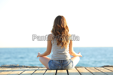 back view of teen practicing yoga