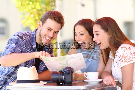 three happy tourists checking guide in