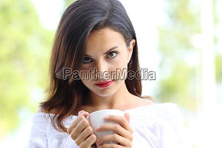 schoene frau haelt kaffeetasse schaut sie