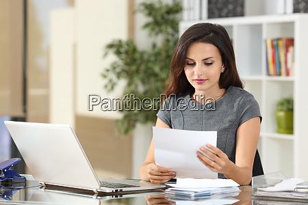 geschaeftsfuehrerin liest einen brief im buero