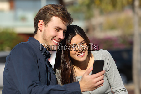 happy couple consulting phone content in