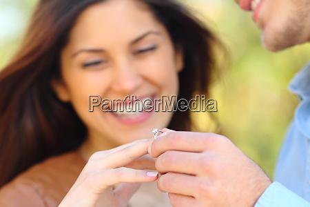 mann setzt verlobungsring zu seiner frohen