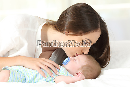affectionate mother kissing her baby sleeping