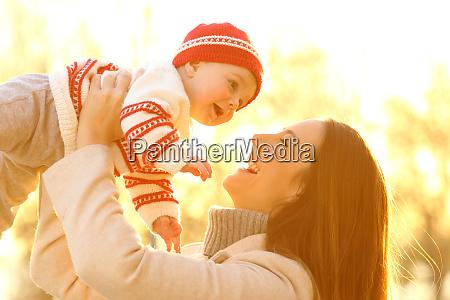 mutter zieht ihr baby bei sonnenuntergang