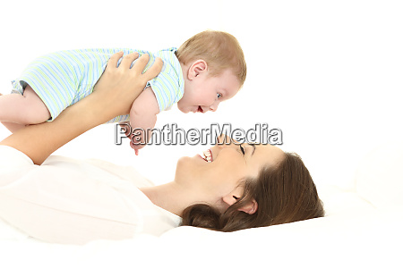 mother and baby lying on bed