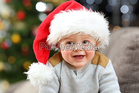 baby wearing santa hat posing at