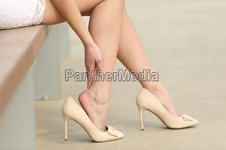 frau traegt high heels beruehren schmerzhafte