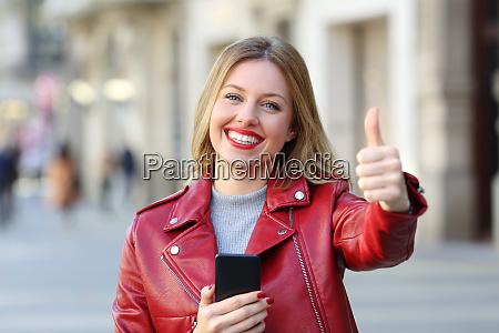 woman holding smart phone with thumb