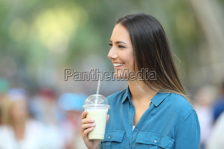 happy woman holding a smoothie looking
