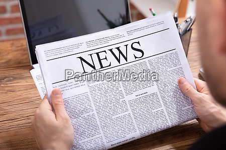 man reading news paper on wooden
