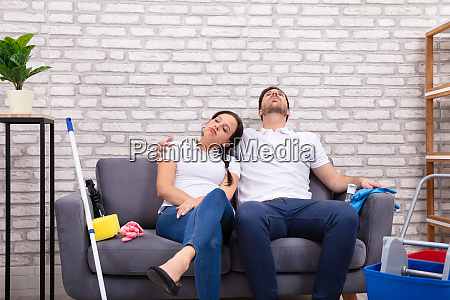 tired couple sitting on sofa
