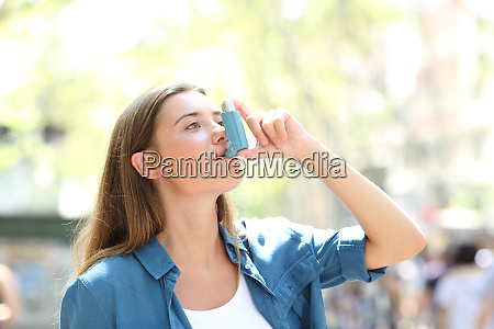 asthmatic woman using inhaler standing in