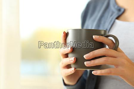 frau haende halten einen kaffeebecher zu