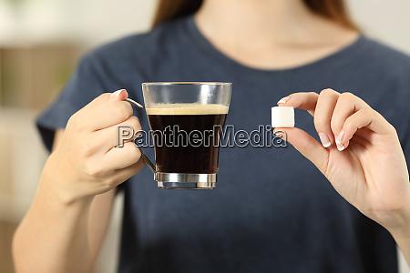 frauenhaende halten kaffeetasse und einen zuckerwuerfel