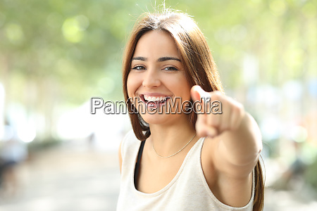 pretty girl pointing at camera outdoors