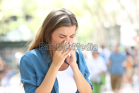 ill woman blowing on a tissue