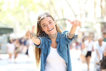 joyful girl gesturing thumbs up in