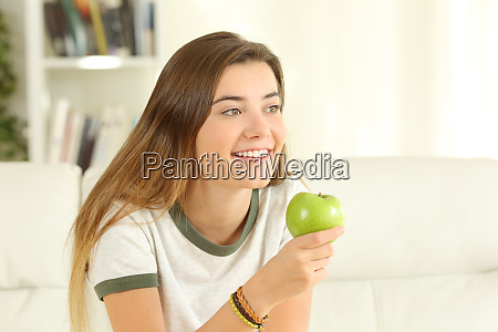 happy teen holding an apple looking